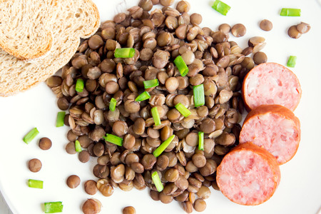 Green lentil with homemade sausage (cotechino) on white plate