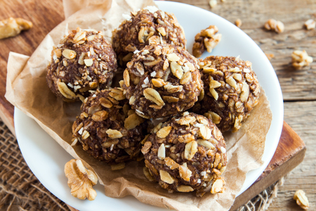 Healthy organic energy granola bites with nuts, cacao, banana and honey - vegan vegetarian raw snack or meal Stock Photo