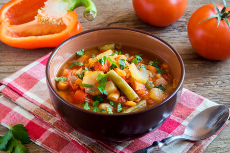 Vegetable soup with ingredients carrot tomato potato parsley pepper celery green beans parsley over rustic wooden background with copy space - healthy vegetarian vegan diet homemade meal soup food