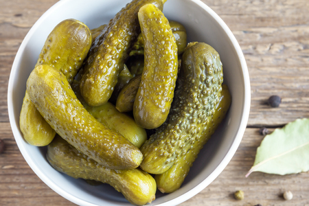 marinated gherkins: Pickles. Bowl of pickled gherkins (cucumbers) over rustic wooden background close up.