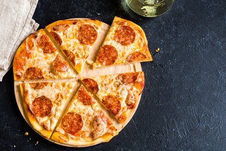 Pepperoni Pizza - Fresh homemade pizza with pepperoni, cheese and tomato sauce on rustic black stone background with copy space. Stock Photo