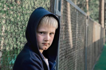 Sad, upset, frustrated boy (child, kid, teen) near metal mesh, close up portrait, children teenager problems concept. photo