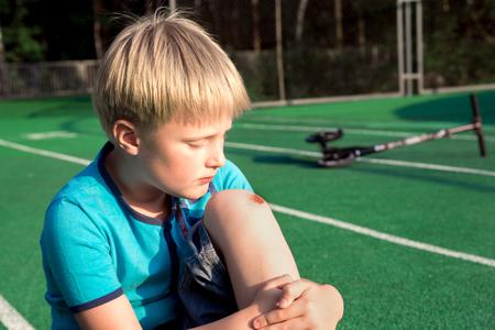 hemorragias: Niño con una herida en la rodilla al aire libre. Herida en la rodilla niño después del accidente.