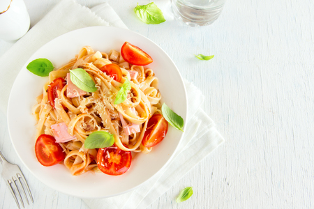 Tagliatelle pasta with ham, tomato sauce, cherry tomatoes and basil leaves on white plate - homemade delicious tagliatelle pasta