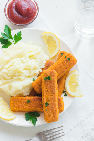 Fried fish fingers, mashed potatoes and lemon. Delicious lunch with fish sticks and vegetables, convenient seafood