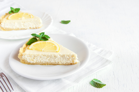 Delicious homemade lemon cheesecake with slices of lemon and mint on white background. Cheese cake. Vanilla and lemon cheese cake.