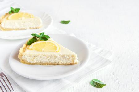 Köstlicher selbst gemachter Zitronekäsekuchen mit Scheiben der Zitrone und der Minze auf weißem Hintergrund. Käsekuchen. Vanille- und Zitronenkäsekuchen.