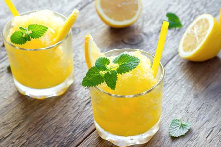 レモン冷凍グラニタ スラッシュで飲む素朴な木製のテーブルの上のグラス。自家製イタリア グラニタ デザート、スラッシュを飲んで夏をさわやか 写真素材
