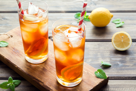 Iced tea with lemon slices, mint and ice cubes on wooden rustic background close up. Homemade refreshing summer drink. Stockfoto