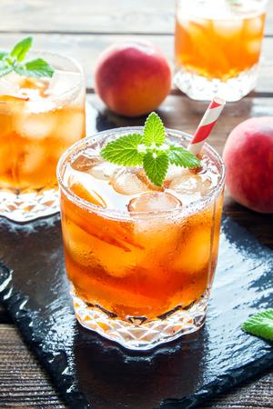 복숭아 아이 스티. 복숭아 슬라이스, 민트와 얼음 조각 슬레이트와 목조 소박한 배경에 아이스 큐브를 닫습니다. 수제 상쾌한 여름 음료.