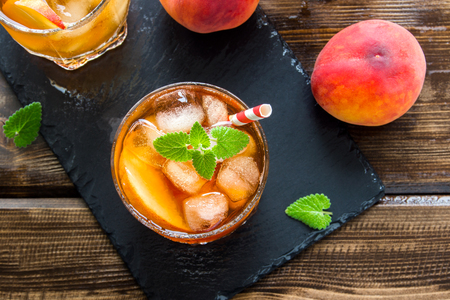 Peach iced tea. Iced tea with peach slices, mint and ice cubes on slate and wooden rustic background close up. Homemade refreshing summer drink.