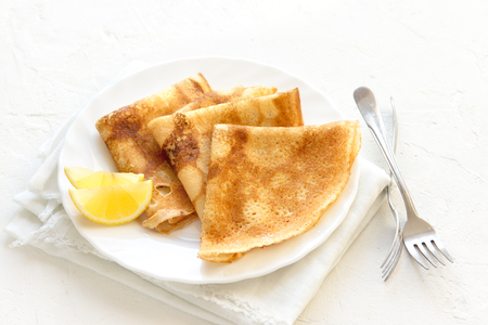 Crepes Suzette with lemon on white plate over white background, copy space. Delicious homemade Crepes for breakfast. Standard-Bild