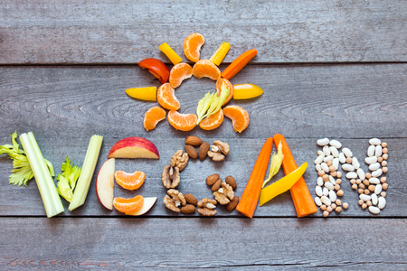 The word Vegan written with vegetables, fruits, nuts and legumes on rustic wooden background, concept - organic ingredients for healthy vegan food and lifestyle