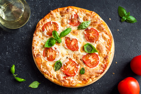 Pizza Margherita on black stone background. Homemade Pizza Margarita with Tomatoes, Basil and Mozzarella Cheese. Stock fotó