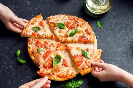 Menschen Hände nehmen Scheiben von Pizza Margherita. Pizza Margarita und Hände close up über schwarzem Hintergrund. Standard-Bild - 80005468
