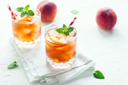 Pfirsicheistee. Iced Tee mit Pfirsich Scheiben, Minze und Eiswürfel auf weißem Hintergrund close up. Hausgemachter erfrischender Sommergetränk.