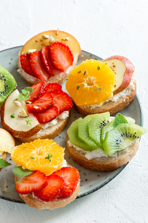 Fruit dessert sandwiches with ricotta cheese. Delicious healthy breakfast toasts with cream cheese, fresh organic fruits and berries, herbs, nuts and bee pollen. Diet healthy food, breakfast, snack.