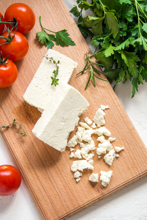 Fresh Greek Feta Cheese. Healthy ingredient for cooking salad. Crumbled Goat feta cheese on cutting board. Stock Photo
