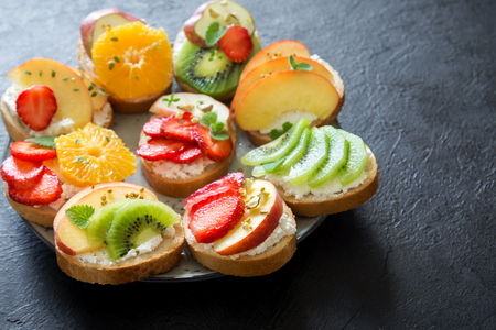 Fruit dessert sandwiches or bruschetta with ricotta cheese. Delicious healthy breakfast toasts with cream cheese, organic fruits and berries, herbs, nuts and bee pollen. Diet healthy food, breakfast, snack.