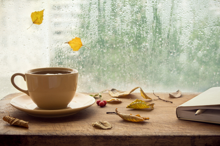 Cup of autumn tea (coffee, chocolate) with note book and yellow dry leaves near a window, copy space. Hot drink for autumn cold rainy days. Hygge concept, autumn mood.