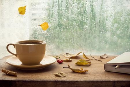 Taza de té de otoño (café, chocolate) con cuaderno y hojas secas amarillas cerca de una ventana, copie el espacio. Bebida caliente para los días fríos y lluviosos de otoño. Concepto de higiene, humor otoñal. Foto de archivo