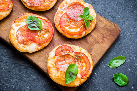 Mini Pizza - Fresh homemade mini pizzas with pepperoni, cheese, tomatoes and basil on rustic black stone background. Stock Photo