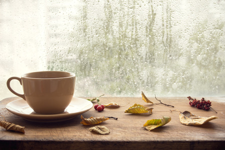 Cup of autumn tea (coffee, chocolate) and yellow dry leaves near a window, copy space. Hot drink for autumn cold rainy days. Hygge concept, autumn mood. Stock Photo