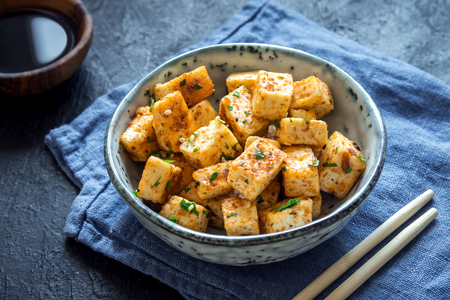 Stir Fried Tofu in a bowl with sesame and greens. Homemade healthy vegan asian meal - fried tofu.