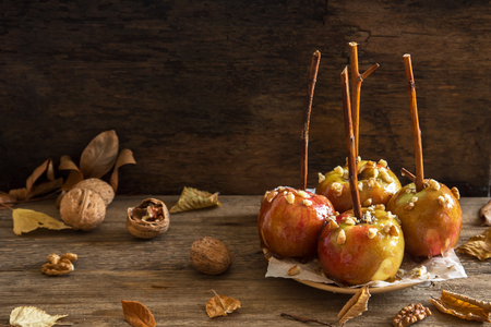 Homemade Caramel Apples on a Stick for Halloween. Organic Snack - Caramel Apples with Walnuts. Stock Photo