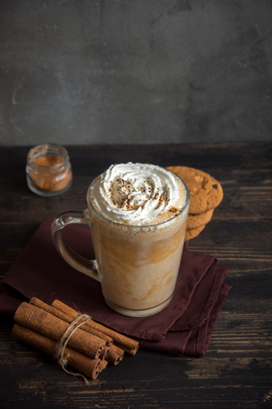 Pumpkin Spice Latte. Cup of Latte with Seasonal Autumn Spices and Cookies. Traditional Coffee Drink for Winter and Autumn Holidays.