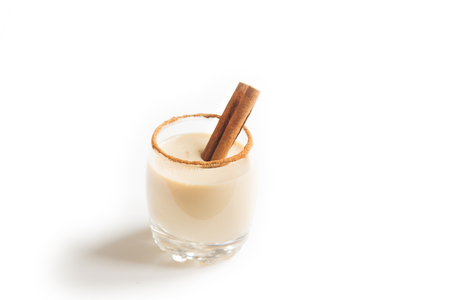 Eggnog with cinnamon and nutmeg for Christmas and winter holidays. Christmas Eggnog isolated on white background.
