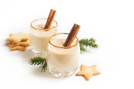 Advocaat met kaneel en nootmuskaat voor Kerstmis en de wintervakanties. Christmas Eggnog, peperkoekkoekjes op witte achtergrond worden geïsoleerd die. Stockfoto