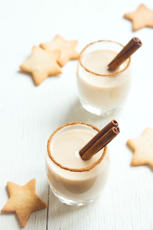 Eggnog with cinnamon and nutmeg for Christmas and winter holidays. Christmas Eggnog, gingerbread cookies on white background.