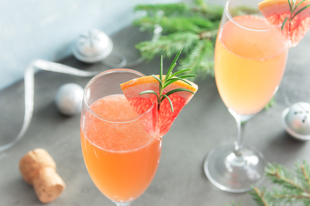 desk: Mimosa festive drink for Christmas - Champagne cocktail Mimosa with Grapefruit and Rosemary for party, copy space