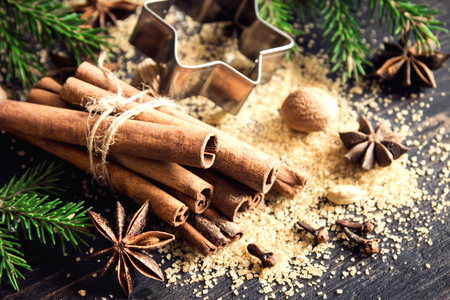 Christmas spices and baking ingredients. Cinnamon sticks, anise stars, nutmeg, cardamom, cloves, brown sugar and cocoa powder for Christmas cake, cookies or mulled wine. Stock Photo
