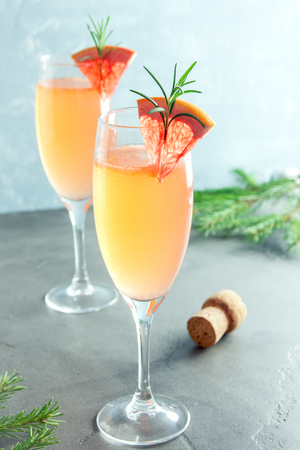 desk: Mimosa festive drink for Christmas - Champagne cocktail Mimosa with Grapefruit and Rosemary for Christmas party, copy space