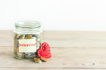 Coins in glass jar with Donation label and red heart. Money savings, charity and donation concept, copy space.
