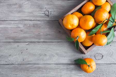 Tangerines (oranges, clementines, citrus fruits) with green leaves over wooden background with copy space