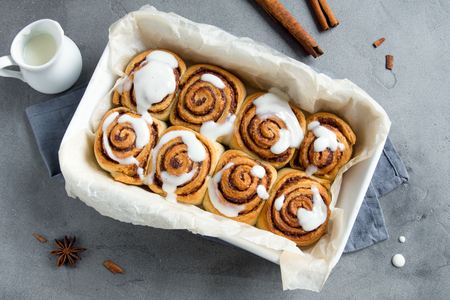 Cinnamon rolls or cinnabons with cream sauce, homemade recipe preparation sweet traditional dessert buns pastry food. Food ingridients for cinnamon rolls on grey concrete table. Archivio Fotografico