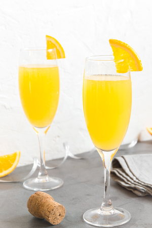 Mimosa drink for party - Champagne cocktail Mimosa with Orange juice over white background, copy space