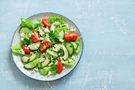 Groene salade met gesneden avocado, tomaten, komkommers en Griekse feta-kaas op blauwe lijst met exemplaarruimte. Gezonde voeding veganistisch vegetarisch zomer fruit salade eten concept.
