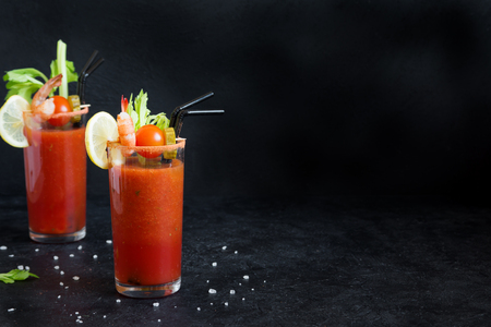 Bloody Mary Cocktail in glasses with garnishes. Tomato Bloody Mary spicy drink on black background with copy space. Stock Photo