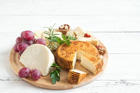 チーズの盛り合わせ、ブドウ、白い木製の背景の上にナッツ、コピースペース。イタリアンチーズとフルーツの盛り合わせ。 写真素材