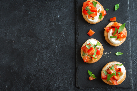 Italian bruschetta with chopped tomatoes, basil, mozzarella cheese and balsamic vinegar. Fresh homemade caprese bruschetta or crostini over black stone background, copy space. Banque d'images