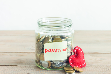 Coins in glass jar with red heart and Donation label. Money savings, charity and donation concept, copy space. Stock Photo