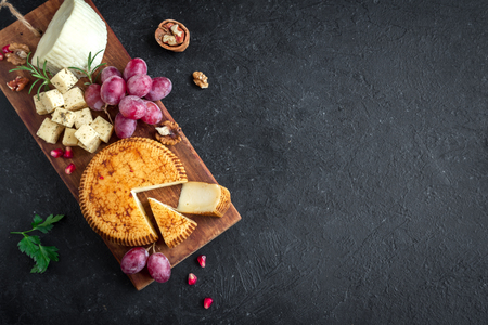 Cheese platter with assorted cheeses, grapes, nuts over black background, copy space. Italian cheese and fruit platter, top view. 写真素材