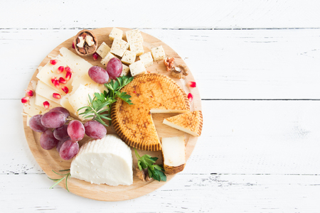 Cheese platter with assorted cheeses, grapes, nuts over white wooden background, copy space. Italian cheese and fruit platter.