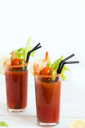Bloody Mary Cocktail in glasses with garnishes. Tomato Bloody Mary spicy drink  isolated on white background with copy space. Stock Photo