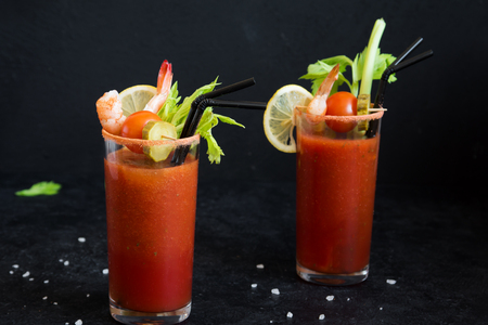 Bloody Mary Cocktail in glasses with garnishes. Tomato Bloody Mary spicy drink on black stone background with copy space. Stock Photo
