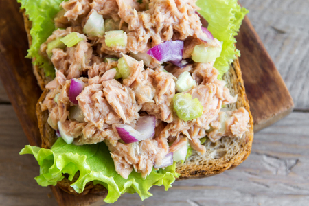 Tuna salad sandwich over wooden background, close up. Homemade sandwich with tuna and vegetables for snack.